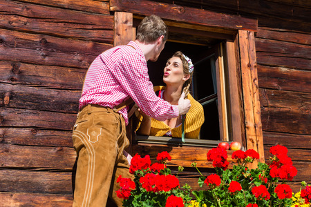 secretly: Couple in love at mountain hut window wearing traditional clothing