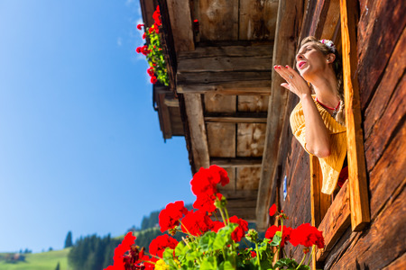 geranium: Woman at window of mountain hut in alps blowing a kiss to lover