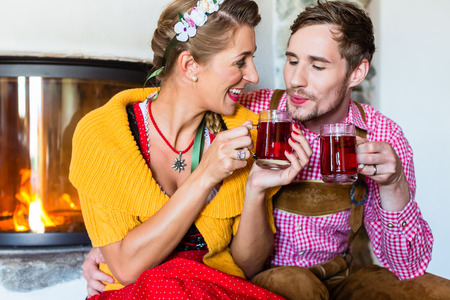woman drinking tea: Man and woman drinking tea at fireplace in cabin Stock Photo