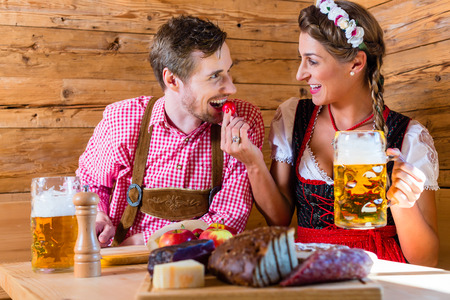 cold cuts: Couple having dinner at mountain hut in alps drinking beer and eating cold cuts