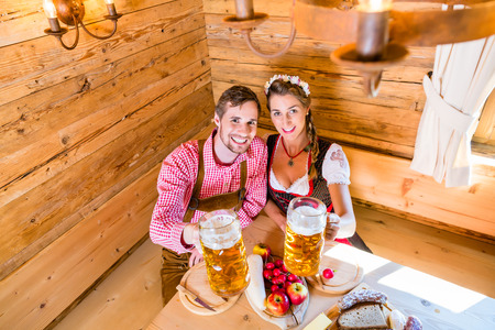 tracht: Couple having dinner at mountain hut in alps drinking beer and eating cold cuts
