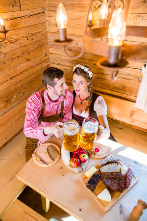 Couple having dinner at mountain hut in alps drinking beer and eating cold cuts photo