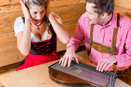 Man playing poorly on zither in mountain hut, his woman in covering her ears with hands photo