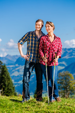 guy with walking stick: Couple enjoying view hiking in the alpine mountains
