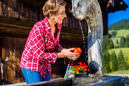 trough: Woman drinking from well in front of mountain cabin Stock Photo