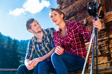 Couple resting from Nordic walking fitness exercise in mountain cabin photo