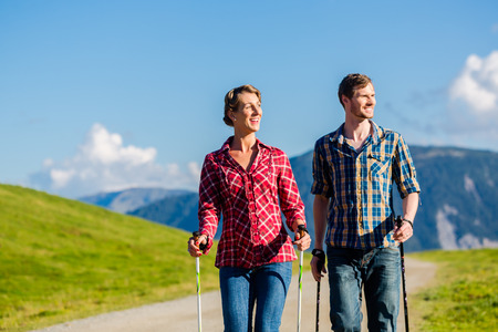 Couple doing Nordic walking exercise in mountains with alpine panorama photo