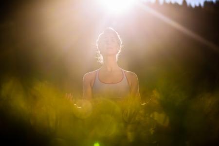 iluminados: Mujer que hace yoga en la puesta del sol, situación retroiluminada
