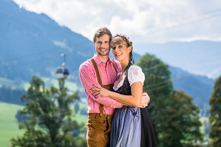 tracht: Couple in Tracht standing on meadow in alp mountains, a cable car is running in the background Stock Photo
