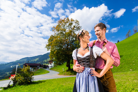 tracht: Couple in traditional Tracht standing on meadow in alp mountains