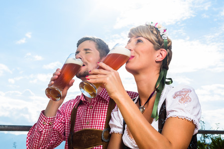Couple on mountain hut in the Alps drinking wheat beer photo
