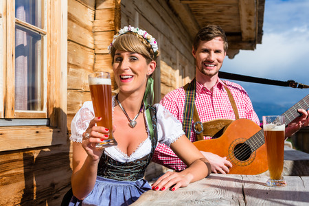 Couple on mountain hut in the Alps making guitar music and drinking wheat beer photo