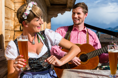 making music: Couple on mountain hut in the Alps making guitar music and drinking wheat beer