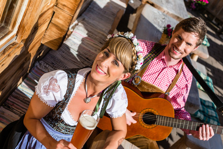 tracht: Couple on mountain hut in the Alps making guitar music and drinking wheat beer