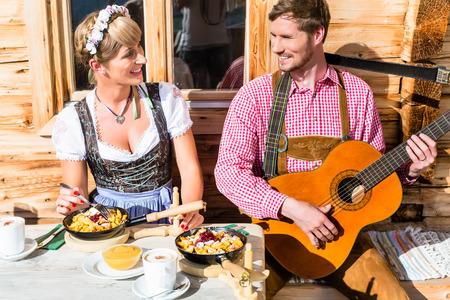Couple on mountain hut eating Kaiserschmarrn, a traditional Austrian pancake photo