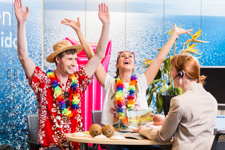 hawaiian lei: Man and woman booking vacation in travel agency cheering for a good deal