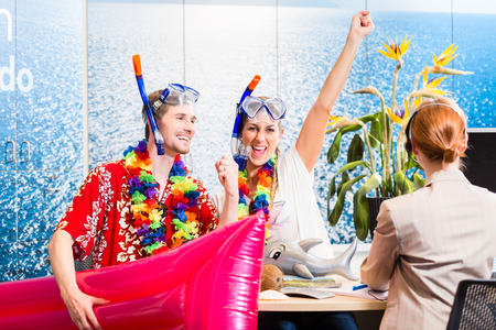 Couple looking forward to beach vacation wearing snorkeling equipment in travel agency photo