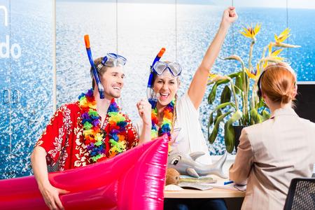 vacaciones playa: Pareja con ganas de vacaciones en la playa con equipo de buceo en la agencia de viajes