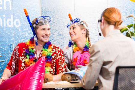 reiseb�ro: Mann und Frau Buchungsstrandurlaub in Reiseb�ro tr�gt ihren Urlaub Outfit