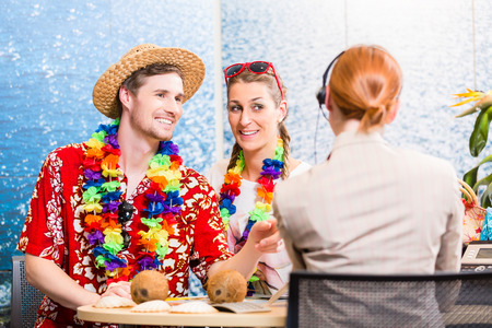 good service: Good service in travel agency - man and woman booking a beach vacation Stock Photo