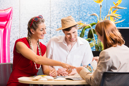 Couple in travel agency booking vacation trip Reklamní fotografie
