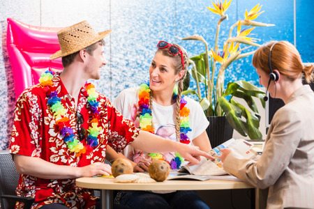 hawaiian lei: Man and woman booking holiday trip in travel agency