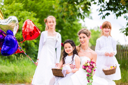 flower baskets: Wedding couple bride with flower children or bridesmaid in white dress and flower baskets Stock Photo