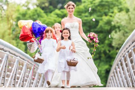 flower baskets: Wedding bride with flower children or bridesmaid in white dress and flower baskets Stock Photo