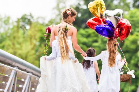 mariée de mariage avec des enfants de fleurs ou de demoiselle d'honneur en robe blanche et des paniers de fleurs