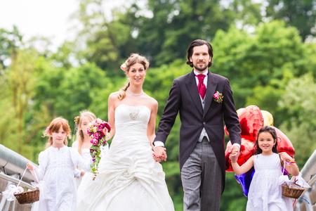 Wedding couple mariée et le marié avec des enfants de fleurs ou de demoiselle d'honneur en robe blanche et des paniers de fleurs