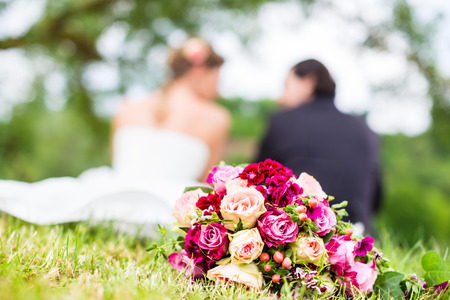 Wedding couple of bride and groom sitting on the meadow with bridal bouquet behind them, candid shot photo