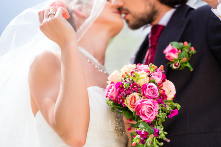 married couples: Bridal pair kissing under veil at wedding Stock Photo
