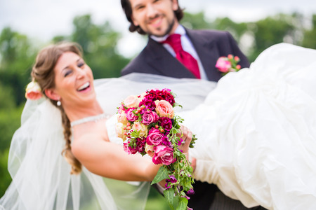 Wedding groom carrying bride on arms photo