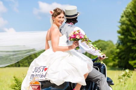 marry: Wedding groom and bride driving motor scooter having fun, a just married sign attached