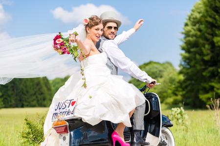 Bruiloft bruidegom en bruid drijvende motor scooter plezier, een net getrouwd teken bevestigd Stockfoto