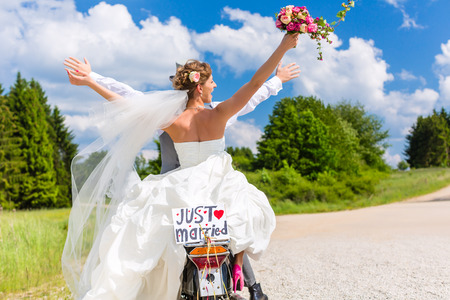 pick: Wedding groom and bride driving motor scooter having fun, a just married sign attached