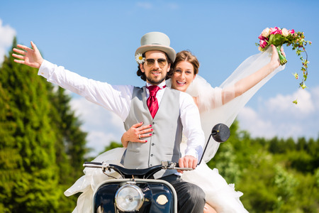 Wedding groom and bride driving motor scooter having fun photo