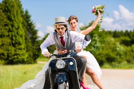 motor scooter: Wedding groom and bride driving motor scooter having fun