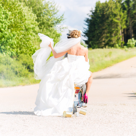 marry: Wedding groom and bride driving motor scooter having fun