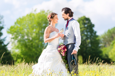 Wedding bride and groom toasting with sparkling wine outside on field photo