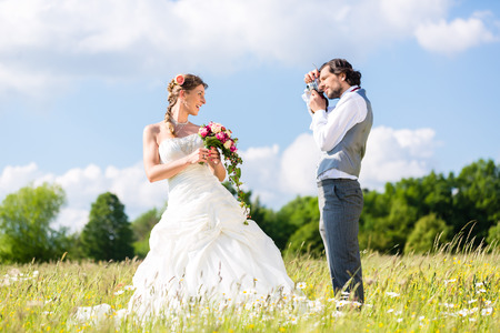Wedding groom photographing bride with camera outside on field or meadow photo