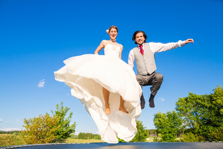 trampoline: Wedding bride and groom jumping on trampoline having fun