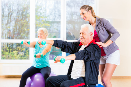 Physiotherapist coaching senior people exercising with dumbbells Stok Fotoğraf
