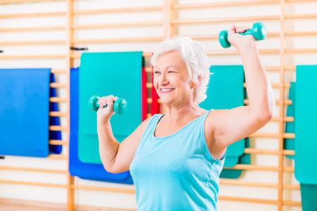 fisioterapia: Mujer mayor que hace deporte de fitness en el gimnasio con pesas Foto de archivo