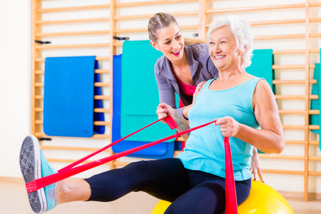 thera: Senior woman with stretch band in fitness gym being coached by personal trainer