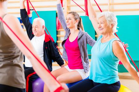 gimnasia: Gente mayor que en curso de la aptitud en gimnasia que ejercita con banda elástica