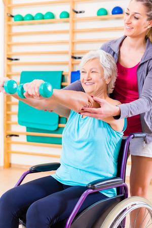 actividad fisica: Mujer mayor en silla de ruedas haciendo terapia f�sica con su entrenador