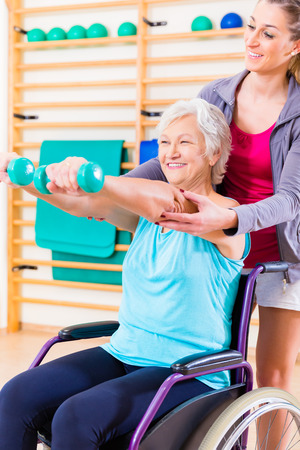 trainers: Senior woman in wheel chair doing physical therapy with her trainer