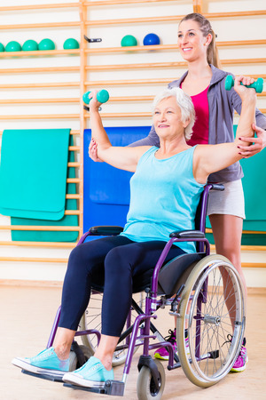 disabled sports: Senior woman in wheel chair doing physical therapy with her trainer