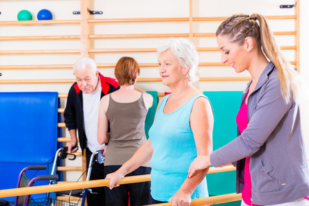 Seniors in physical rehabilitation therapy with trainer photo